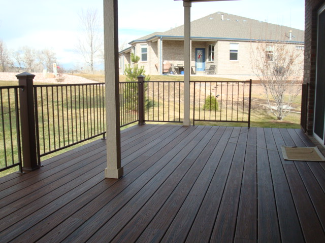 TREX SELECT DECK WITH SADDLE DECKING FASCIA WOODLAND BROWN BORDER FORTRESS BLACK STEEL RAILINGS AND SPIRAL STAIRCASE